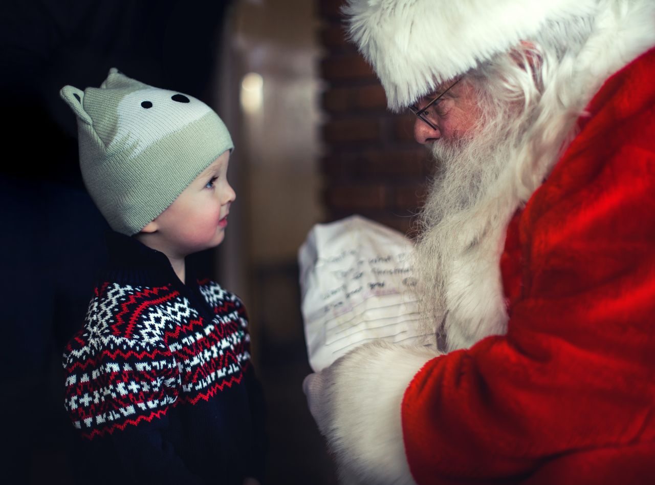 Father christmas gives child present